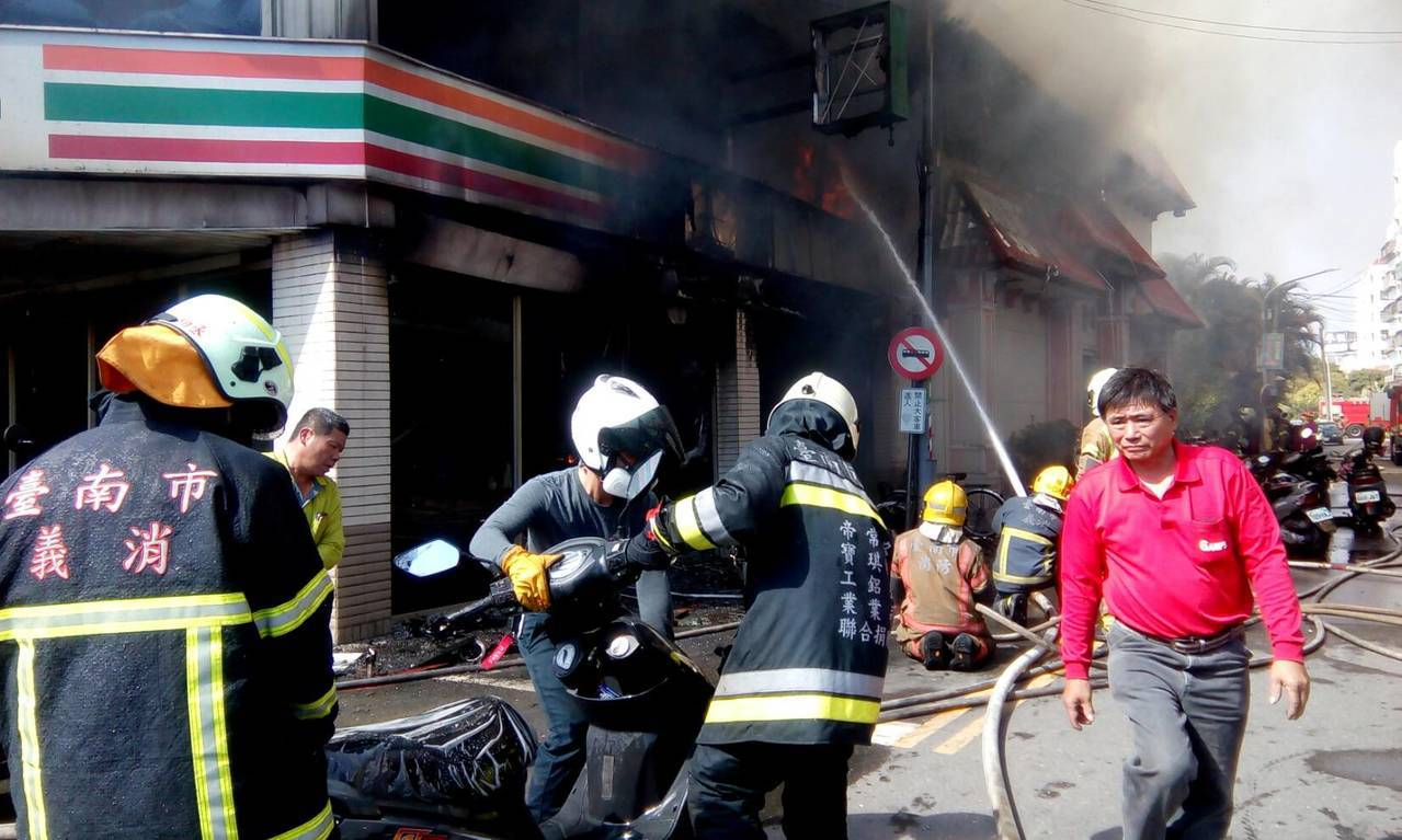 消防隊員搶救停在超商旁機車。記者謝進盛/攝影