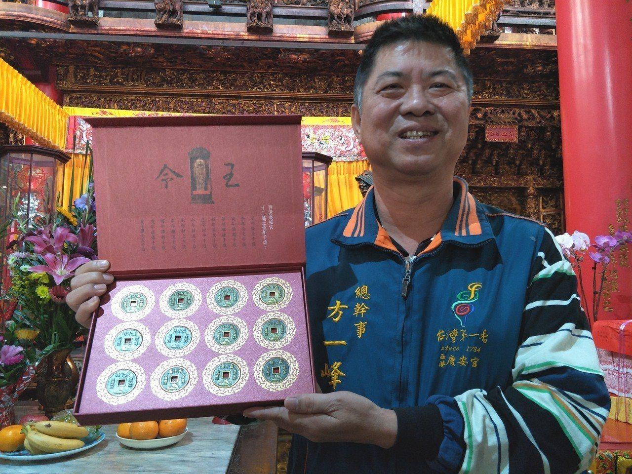台南西港慶安宮每年歲錢圖案由不同神明輪值,總幹事方一峰秀出不同歲錢款式。記者謝進...