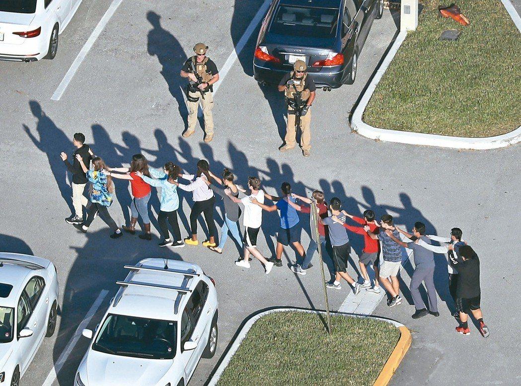 在警方指引下,可見到學生列隊魚貫逃出教室。 (法新社)