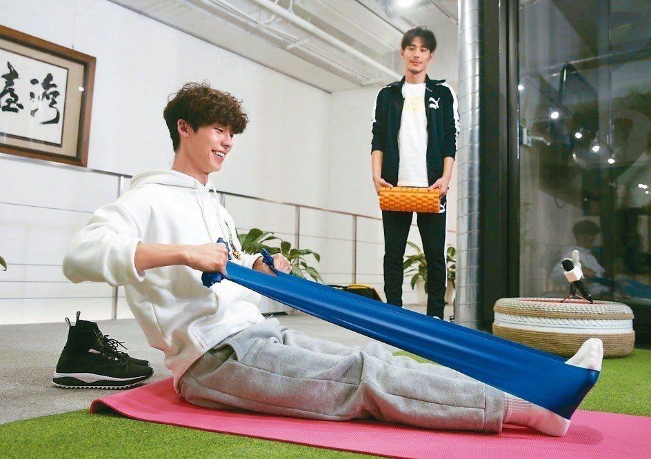 許光漢(左)、黃騰浩示範居家健身,使用彈力帶。 記者邱德祥/攝影