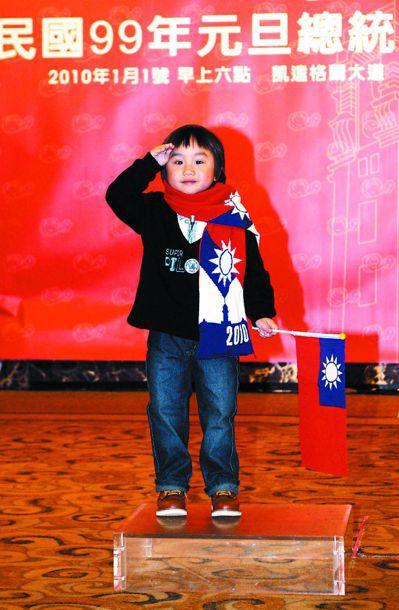 當年小小彬戴國旗圍巾,邀民眾一起來升旗。 (中央社)
