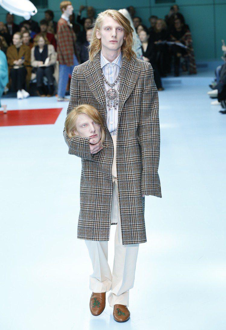 模特兒拎著仿真頭顱出場。圖/Gucci提供