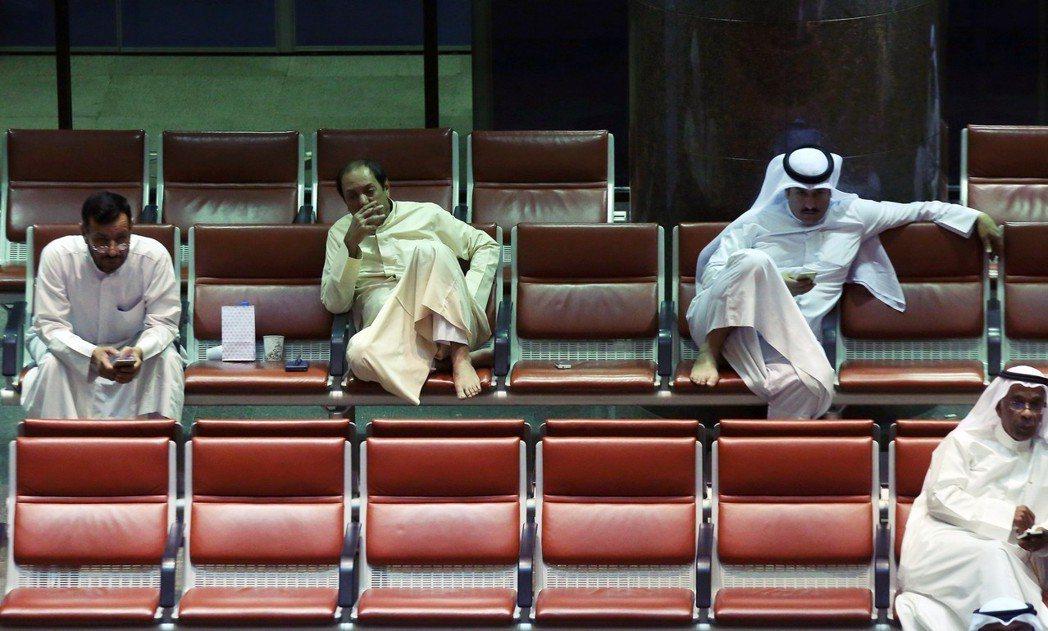 「沒辦法,外國人就是比較便宜,還比科威特人能幹。」圖為科威特證交所內的科威特人。...
