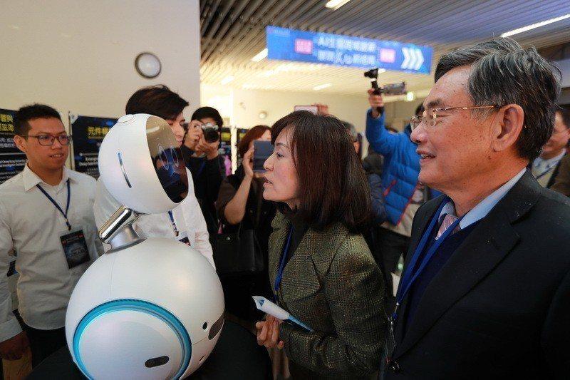 成大校長蘇慧貞(中)對於會回答問題的陪伴照顧機器人大感興趣。 成大/提供