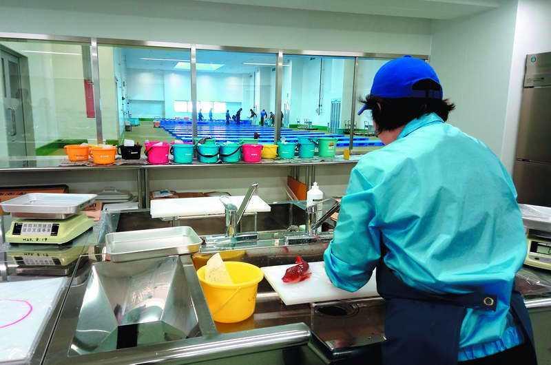 福島縣小名濱漁港的魚市場檢測室,不同顏色的桶裡裝著各種海產,工作人員會當場檢測樣...