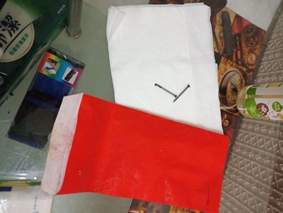 台北一女網友與男友日前在租屋處打掃房間時,發現床底下有一個紅包袋裝著2鐵釘。 圖...