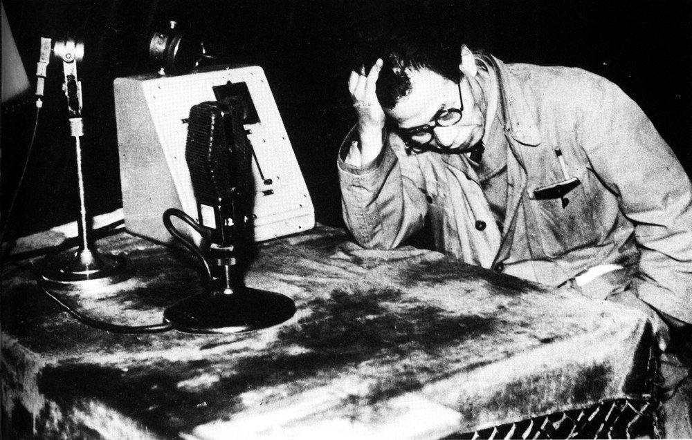 總罷工的委員長伊井彌四郎,右手撐著頭坐在NHK裡,向全國昭告罷工中止。 圖/維基...