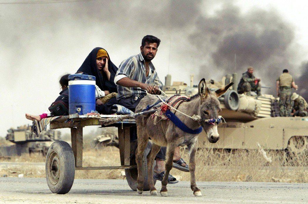 2003年美伊戰爭,烽火中的伊拉克難民。 圖/路透社