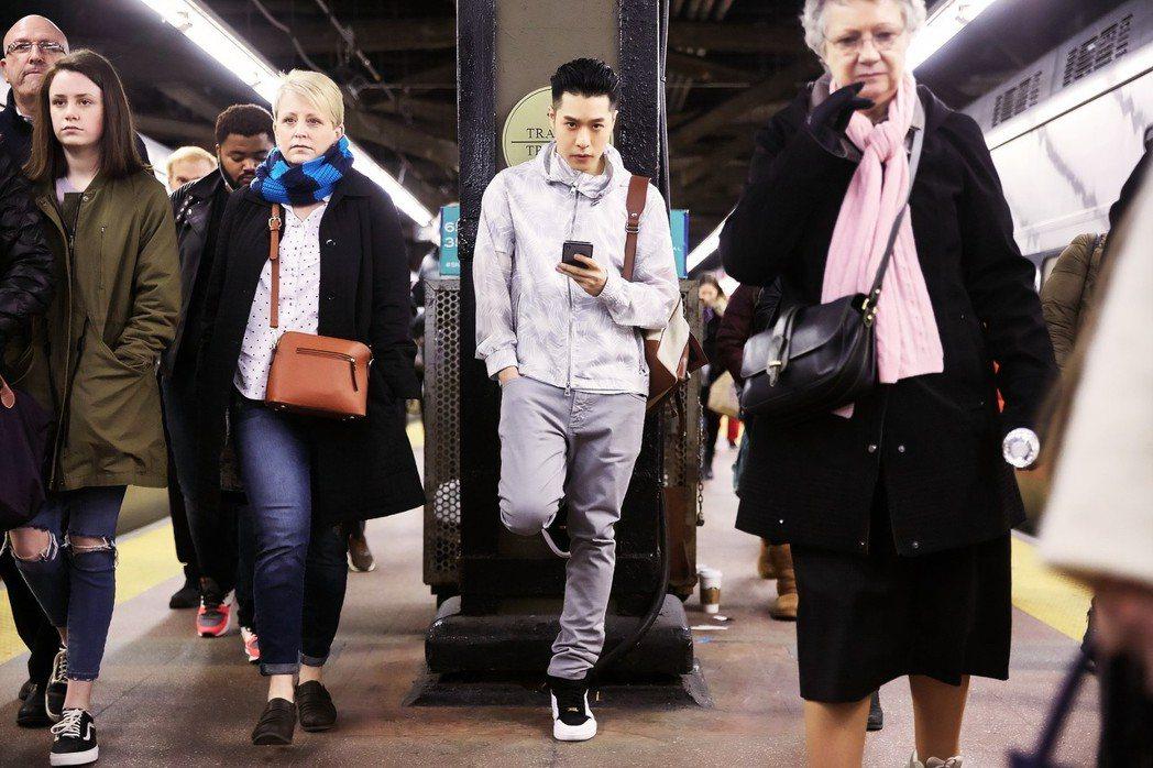 周湯豪於紐約地鐵身穿圖騰白灰色連帽外套街拍。圖/MICHAEL KORS提供