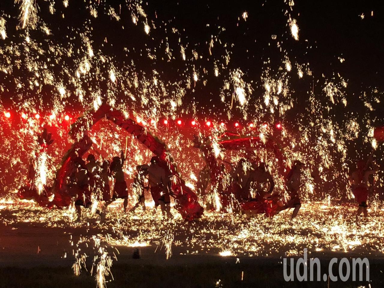 銅梁火龍今晚在南投燈會登場,高溫鐵水濺射化成一陣陣流星火雨,舞者上半身打赤膊,在...