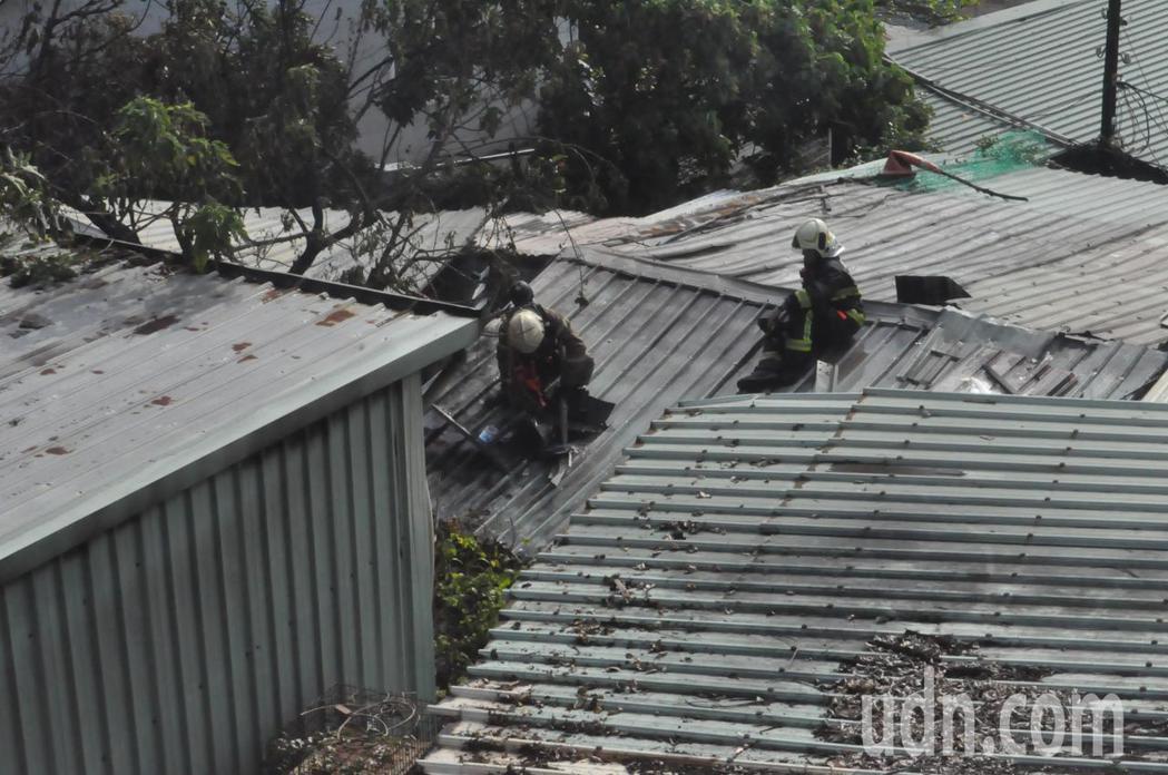 鼓山區民宅火警,消防人員打破鐵皮屋頂降溫。記者黃宣翰/攝影