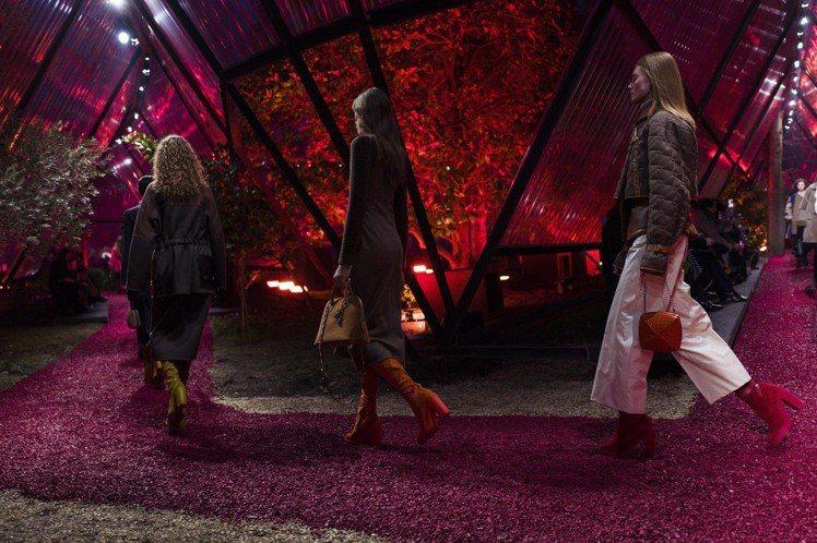 不同於男裝選擇在神秘的修道院建築中發表,愛馬仕女裝在空曠地區搭出映著紅光的建築,...