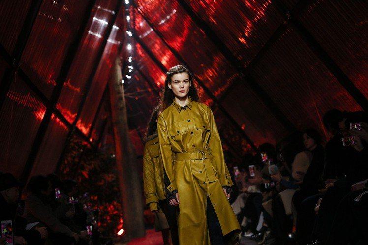 芥末黃的過膝長大衣,剪裁俐落又不失帥氣感,正是愛馬仕女裝這季的重點。圖/美聯社