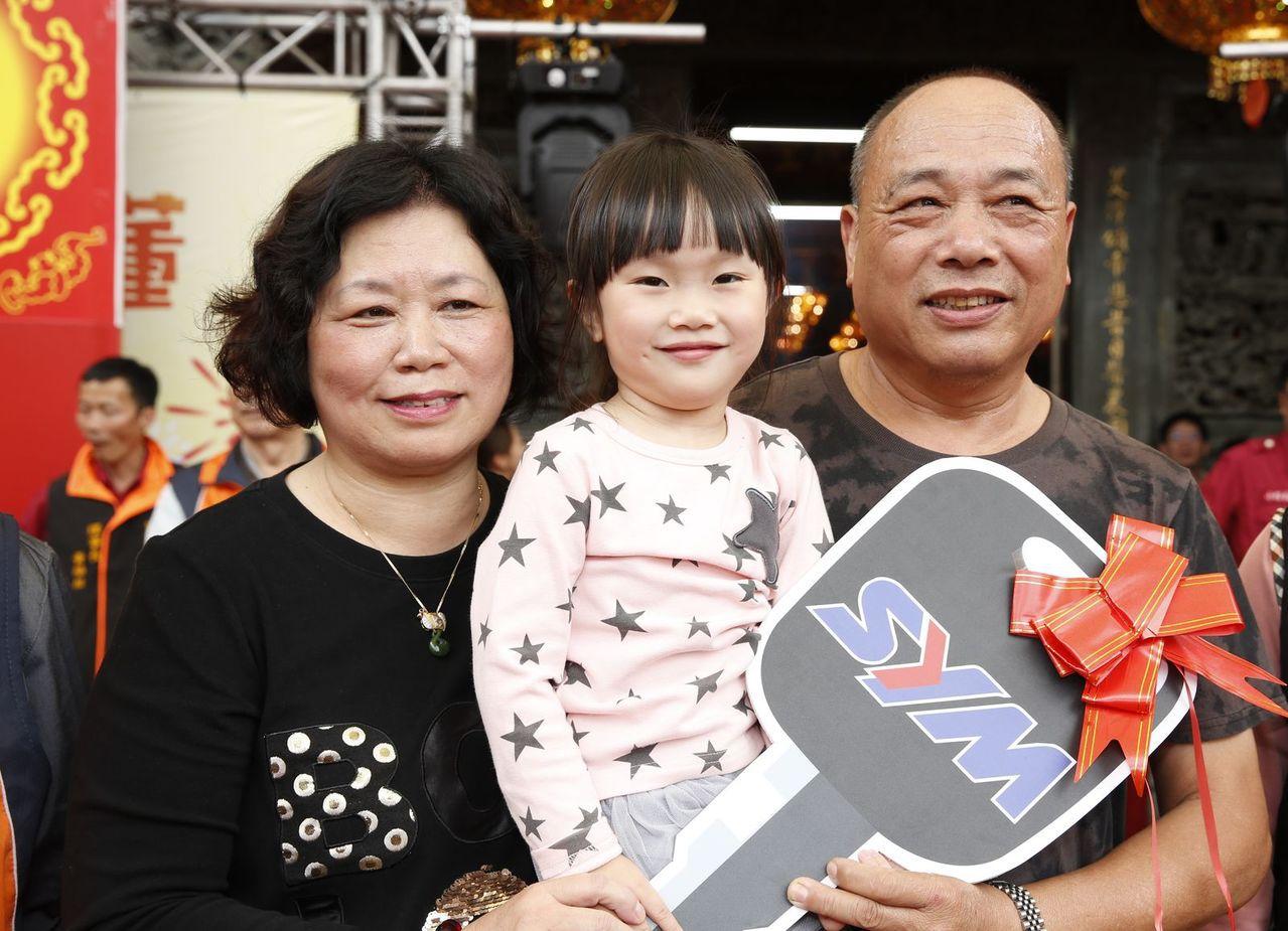 桃園市龍潭區龍元宮千人擲筊杯大賽,由年僅4歲的徐芷希小朋友(中),在家人協助下以...