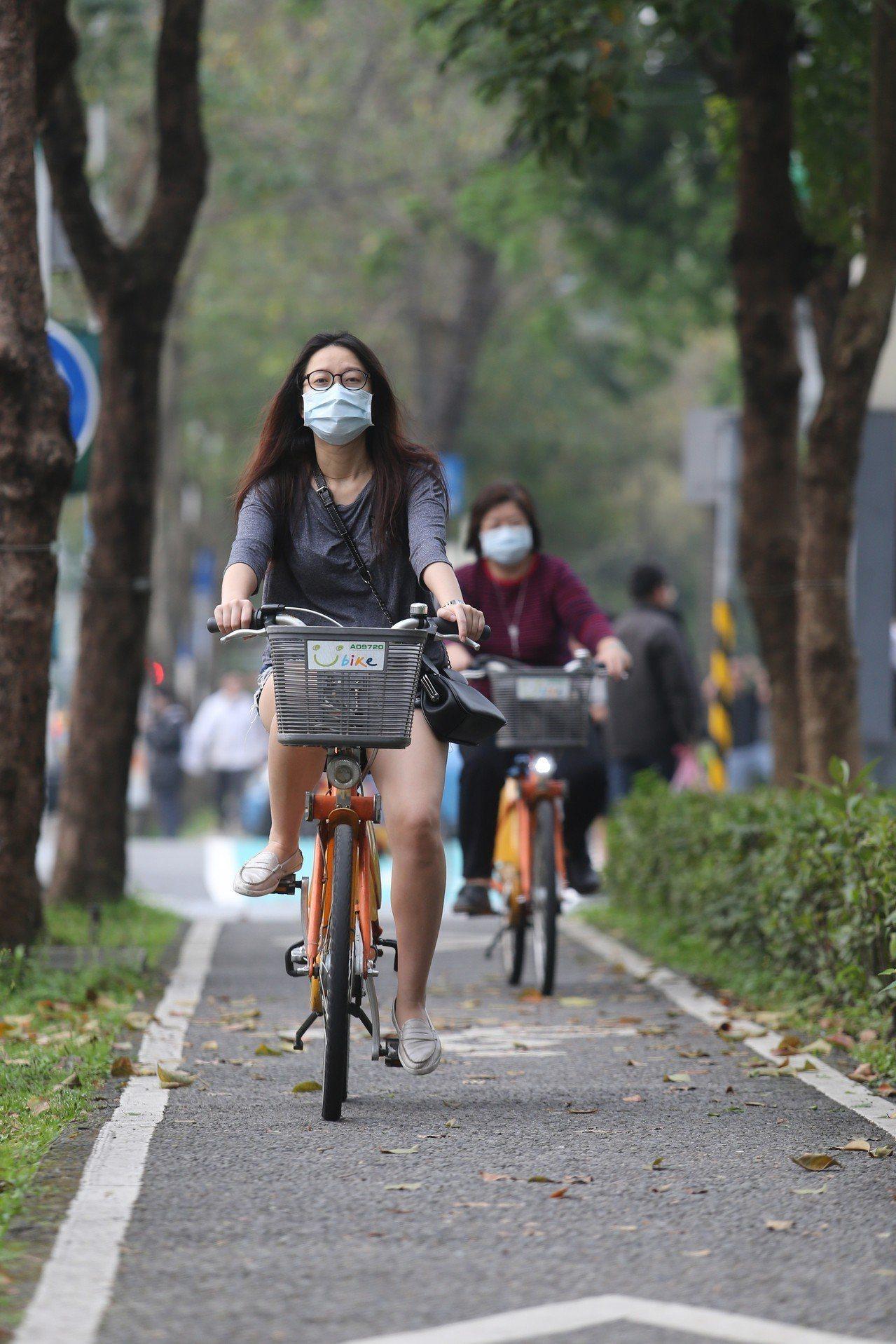 在一片紅害等級的空汙之中,在信義區騎單車的民眾戴起口罩因應,以防糟糕的空氣品質影...