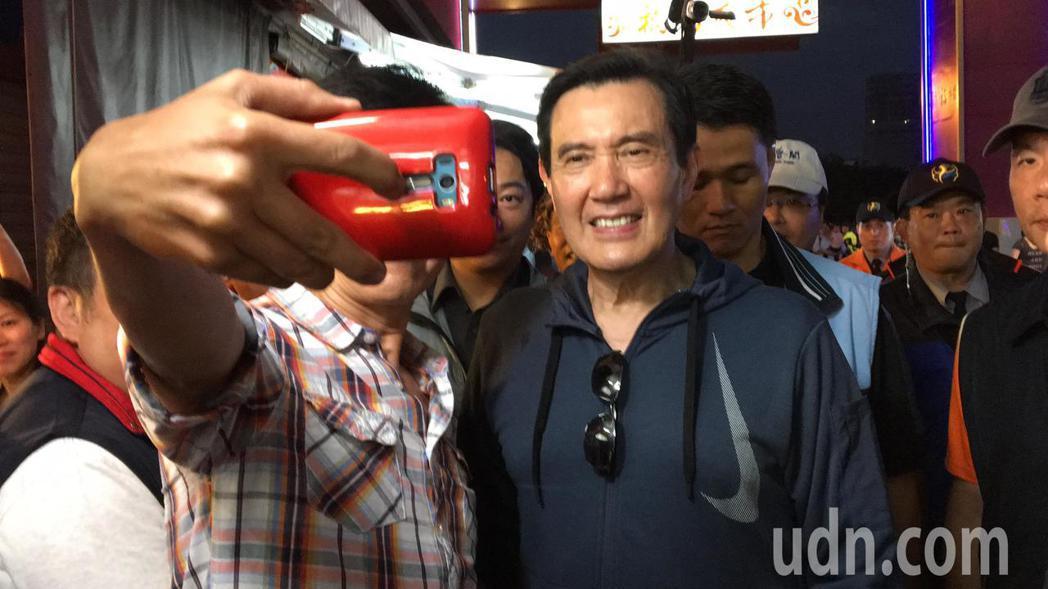 民眾拿起手機自拍與馬英九的合影。記者徐庭揚/攝影
