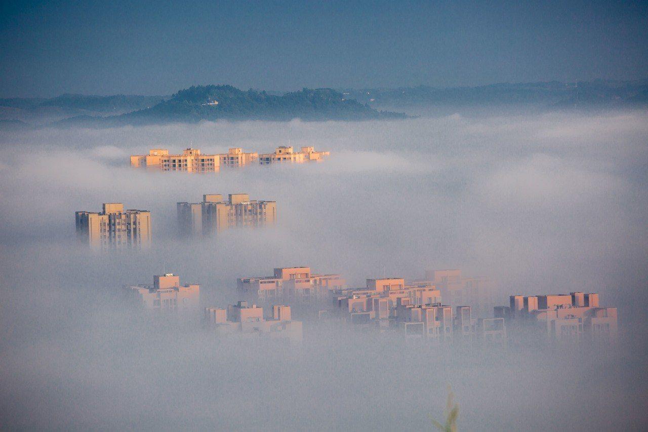 雨後初晴的重慶市大足城區出現平流雲景觀,晨光下的建築物雲遮霧繞。新華社資料照