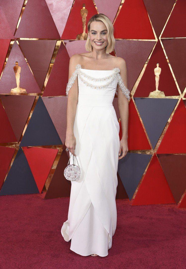 瑪格羅比以一襲白色香奈兒高級訂製服搭配透明Minaudiere鍊帶硬殼包,柔美典...
