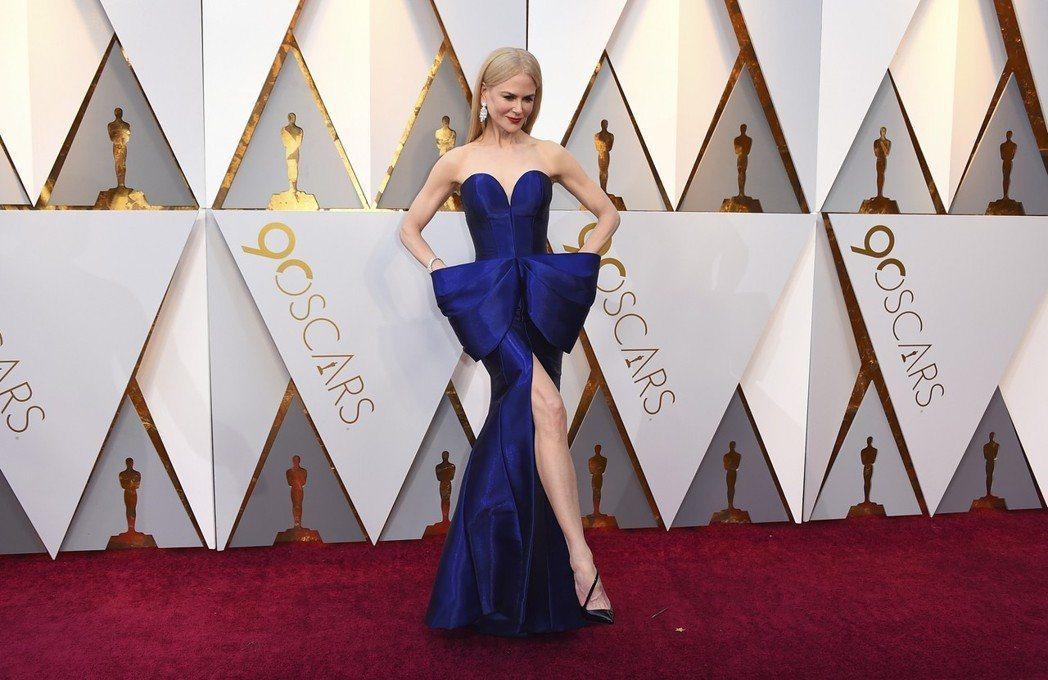 穿著Armani蝴蝶結寶藍色高級訂製服的妮可基嫚,高衩剪裁不時大秀美腿及腳上的紅...