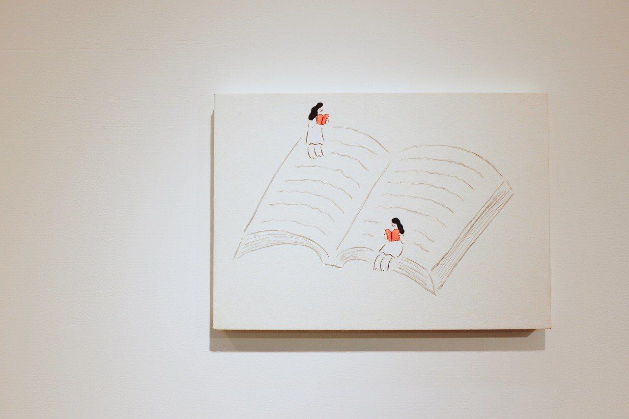 小小人坐在書上,看小小本的書。記者沈佩臻/攝影
