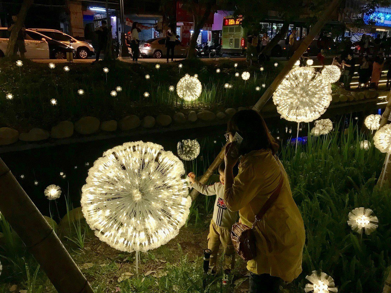 台中綠川爆紅成為熱門景點,入夜後人潮更多,不少人為了拍美照,跨出步道踩草皮,拉著...