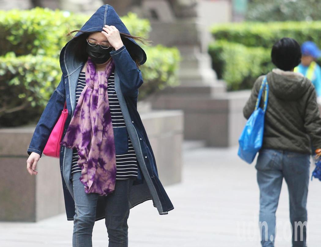 北部民眾外出,明顯感受到氣溫下滑,紛紛裹上厚外套、戴口罩,抵禦寒風。記者陳正興/...