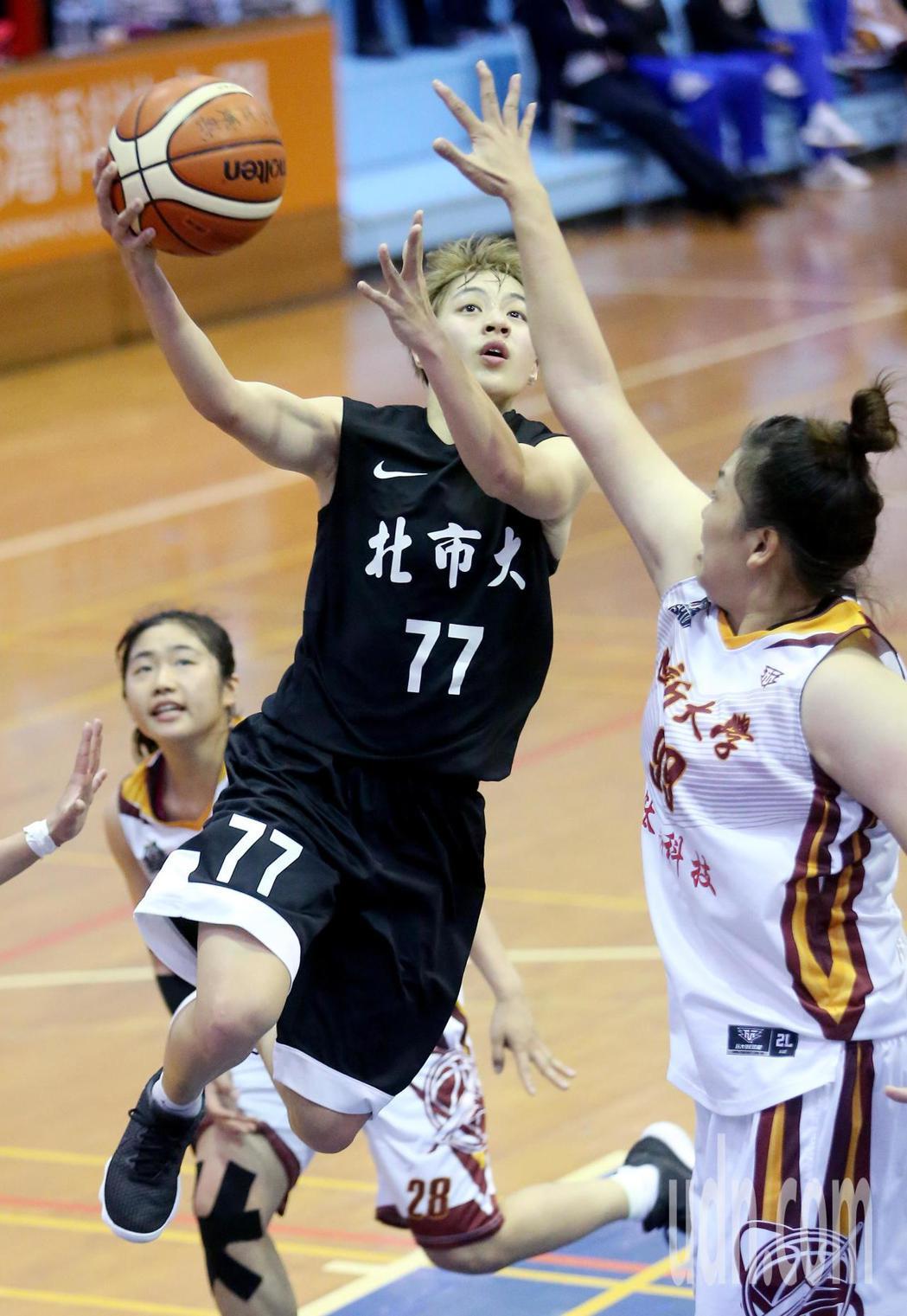 UBA大專籃球聯賽在台灣科大進行女子組賽事,北市大朱育勤(中)突破包夾上籃得分。...