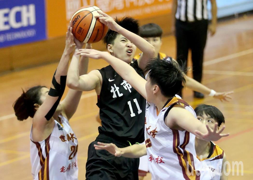 UBA大專籃球聯賽在台灣科大進行女子組賽事,北市大陳亭羽(中)切入時遭到包夾。記...