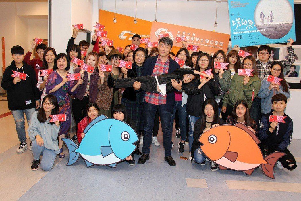 導演賴國安(前排中)抱起童星白潤音,為電影上岸的魚宣傳 大葉大學/提供。