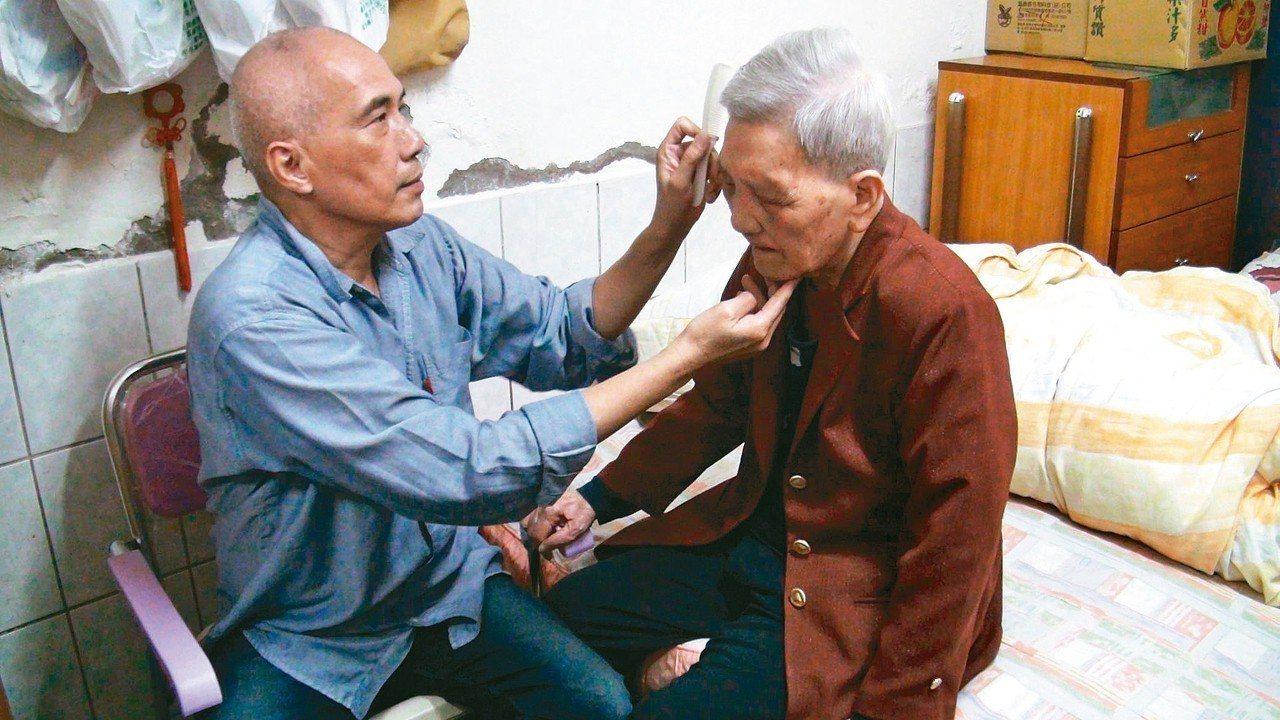 六十七歲男子林憲文(左)照顧高齡九十六歲的失智母親林黃素鶯,悉心地幫母親梳頭髮,...
