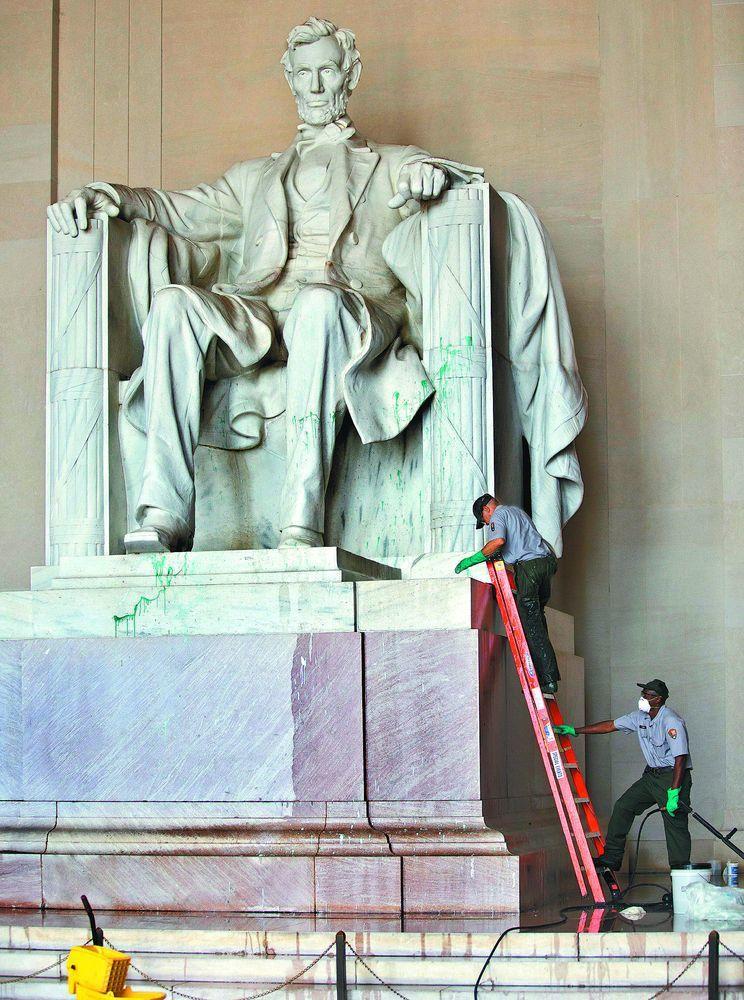 華府林肯紀念堂林肯像當年遭人潑綠漆,工作人員趕緊展開清除。(美聯社)