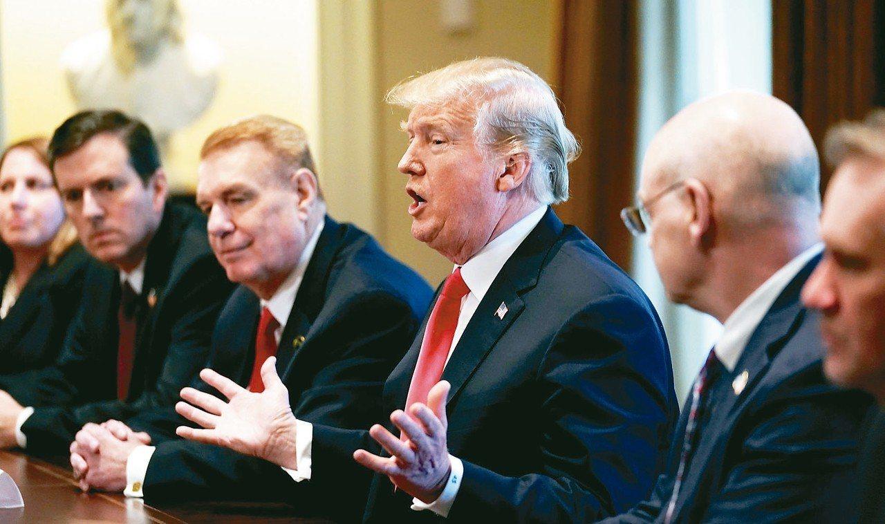 美國總統川普(中)即將簽署文件,對外國鋼鋁課徵重稅。 路透