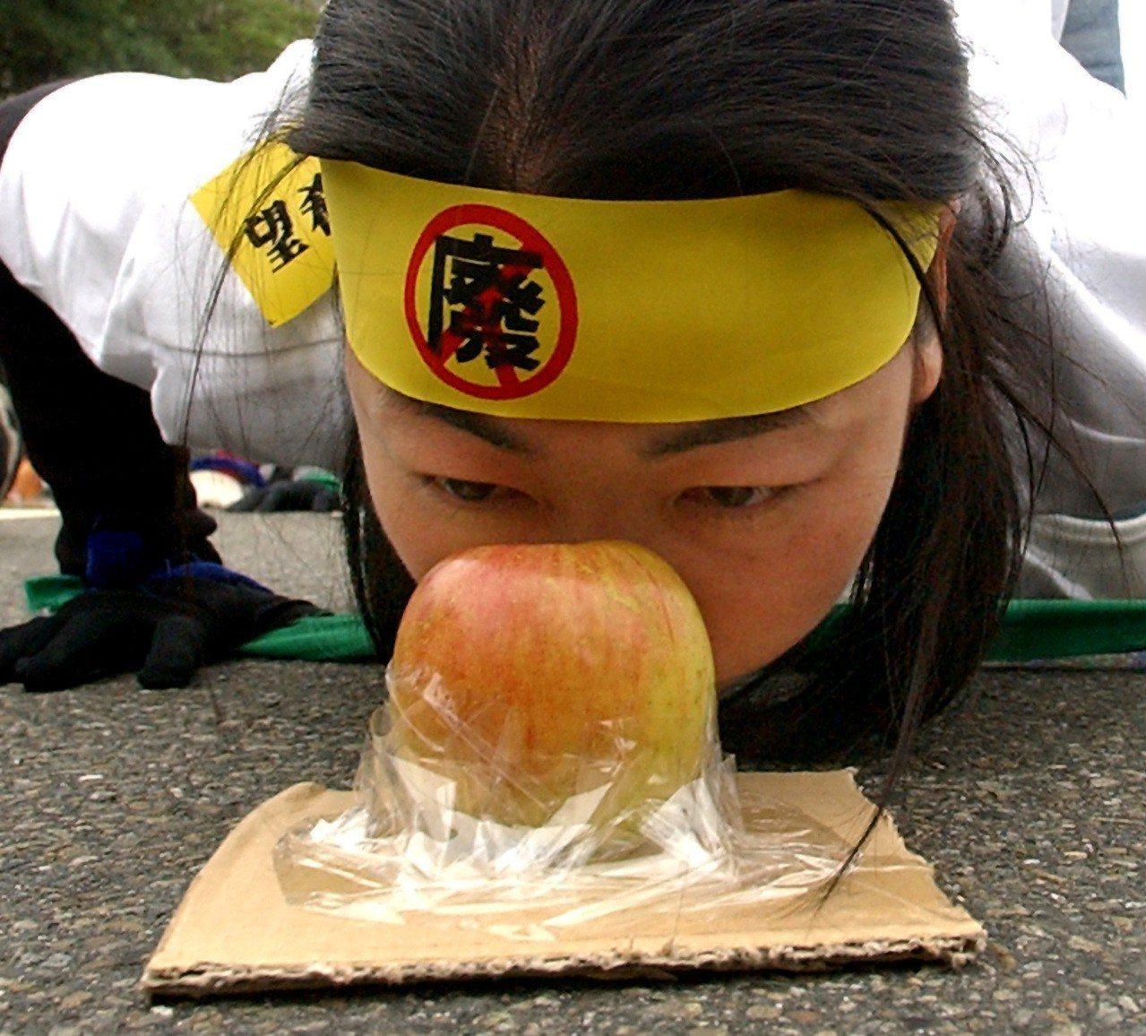 工人春鬥「拒吃爛蘋果,投出新希望」遊行,民眾身體低伏在地,用鼻子將象徵「爛蘋果」...