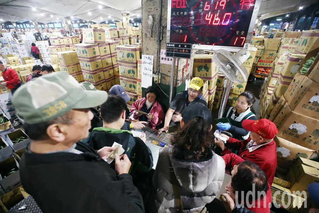 台北果菜批發市場經過三天休市後,凌晨恢復正常交易,到貨量倍增,現場拍賣工作如火如...