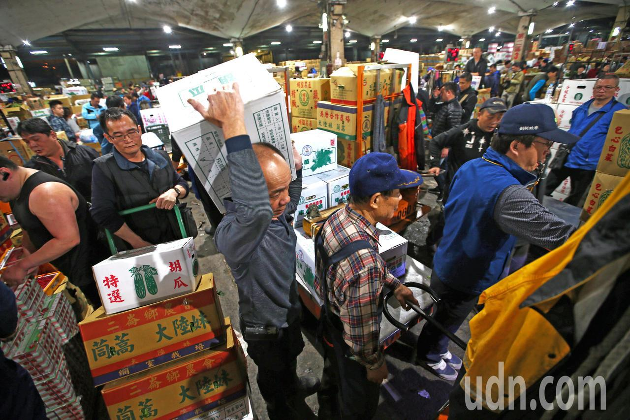 台北果菜批發市場經過三天休市後,凌晨恢復正常交易,到貨量倍增,現場工作人員顯得相...