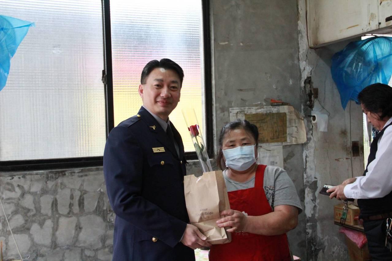 淡水警分局長劉炯炫(左)特地送花和蛋糕給分局對面早餐店老闆娘,感謝她總是很關心員...
