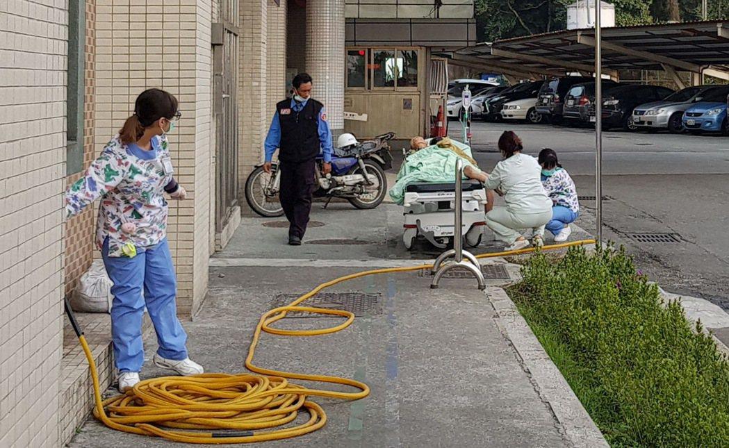 3名護士在醫院急診室外,替送醫的老人洗腳。圖/取自謝輝龍臉書