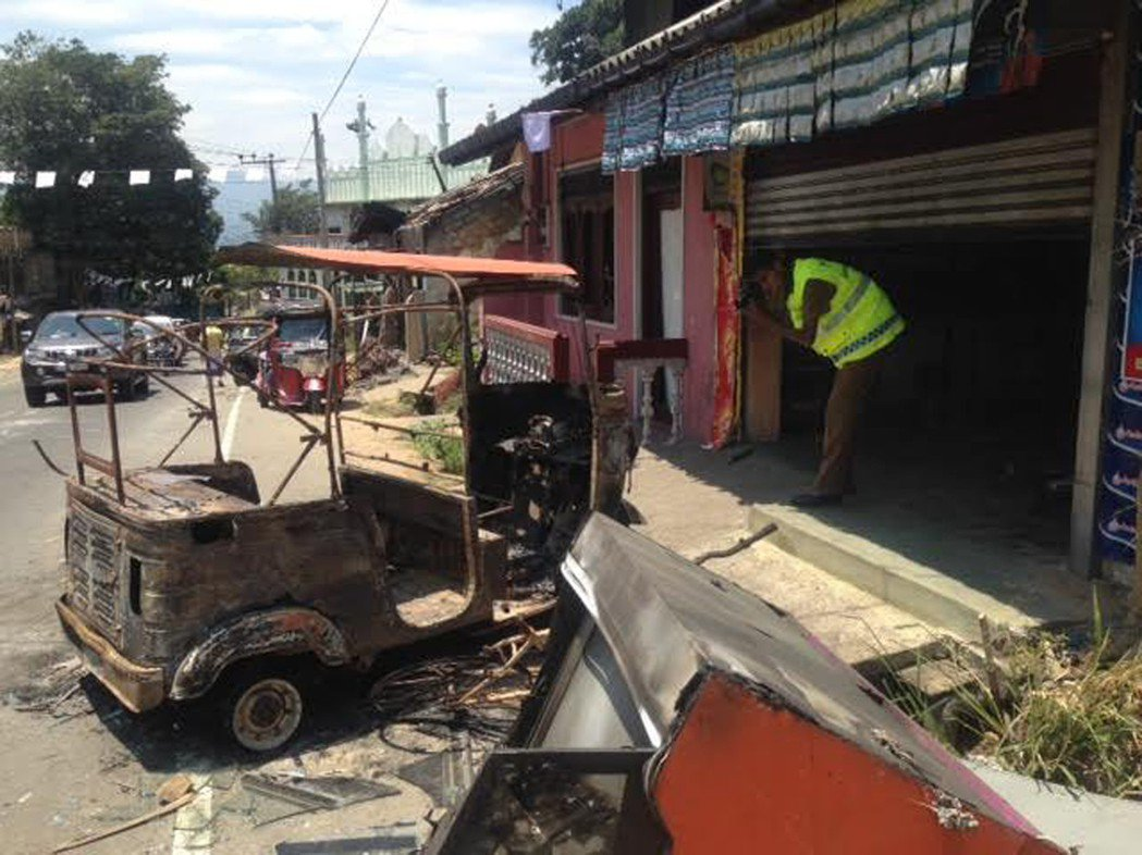 一名警察8日在康提郊區調查一間被縱火的商店,店外的車輛也被燒毀。美聯社