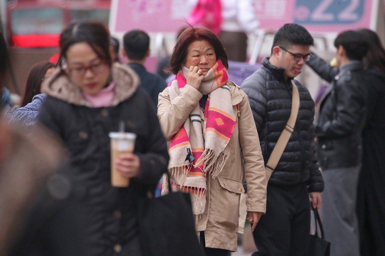 鋒面通過,強烈大陸冷氣團報到,台北市8日下午飄著細雨,氣溫偏低,街頭民眾圍著大圍...