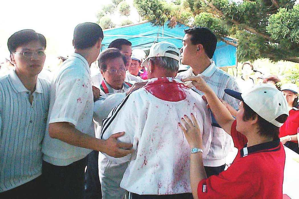 穿著白色運動服的卸任總統李登輝,被抗議人士潑紅墨水,衣領下有一大片紅漬,隨扈在旁...
