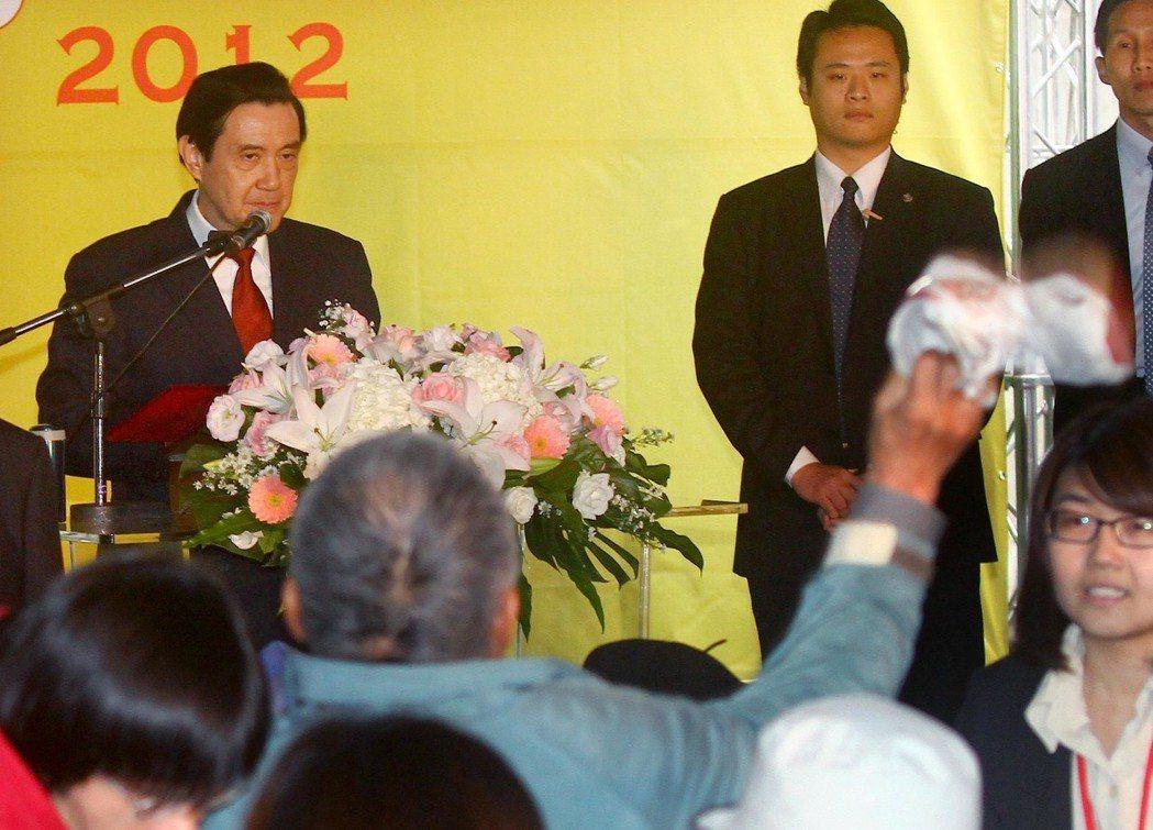 馬英九總統任內(後左)參加「2012世界人權日」開幕儀式,致詞時遭抗議民眾丟鞋子...