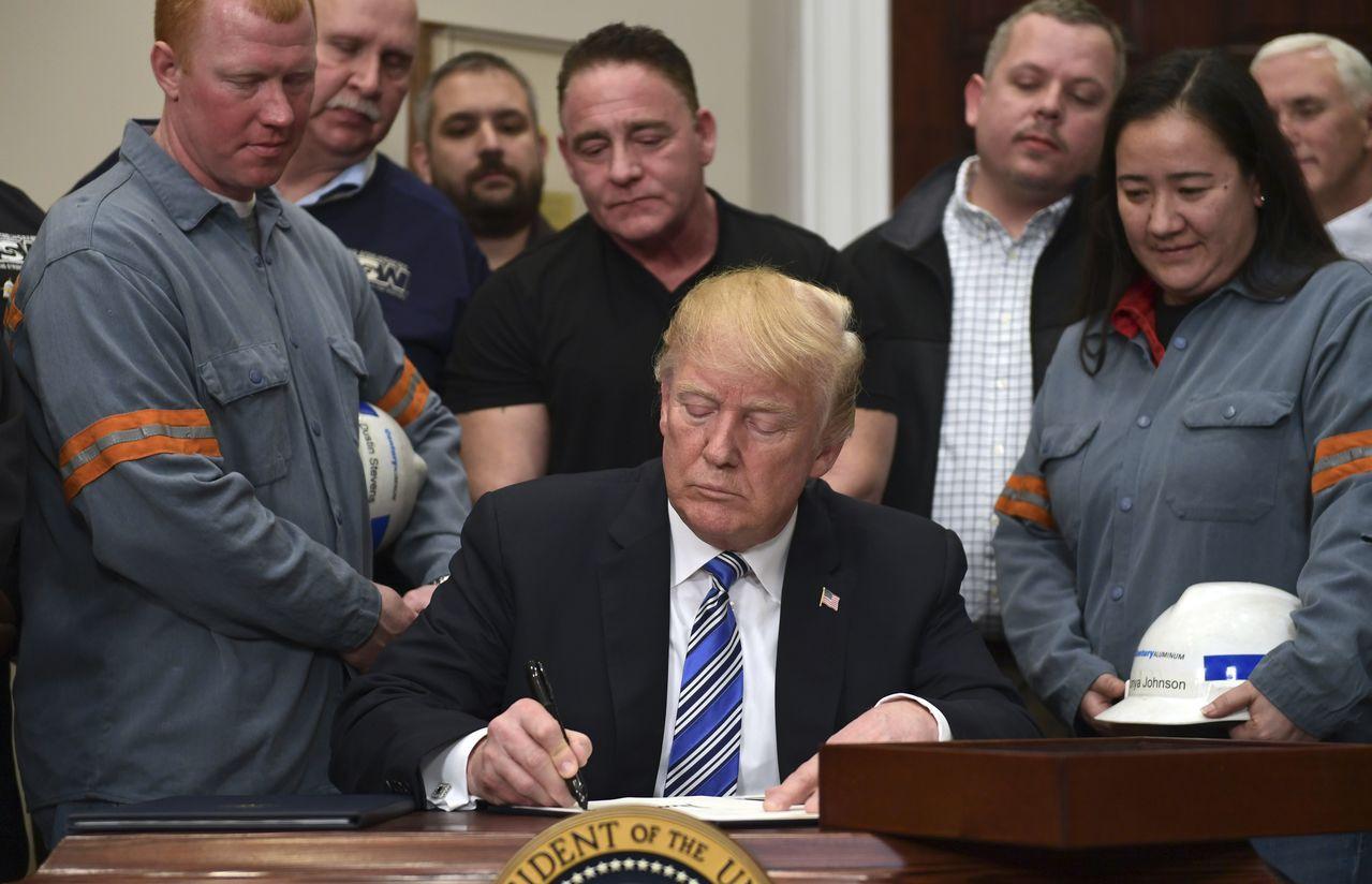 川普在白宮接見鋼鐵和鋁業勞工,並在會上簽署了授權課徵關稅的公告。美聯社