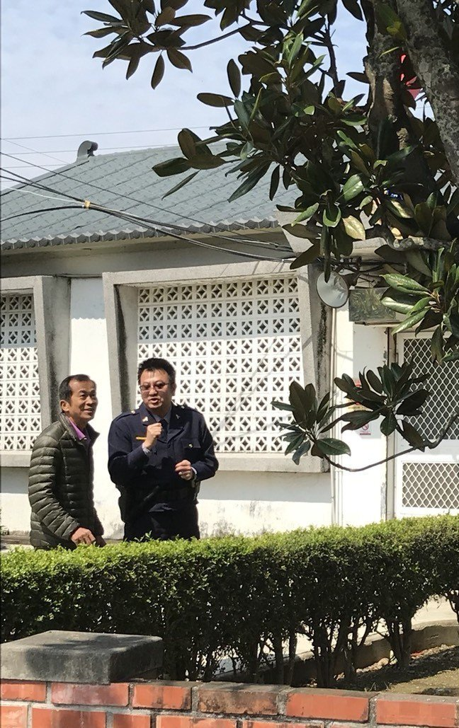 新埤派出所長鄭富強(右)與徐錦昌(左)討論,如何醫治木蓮樹。記者卜敏正/攝影