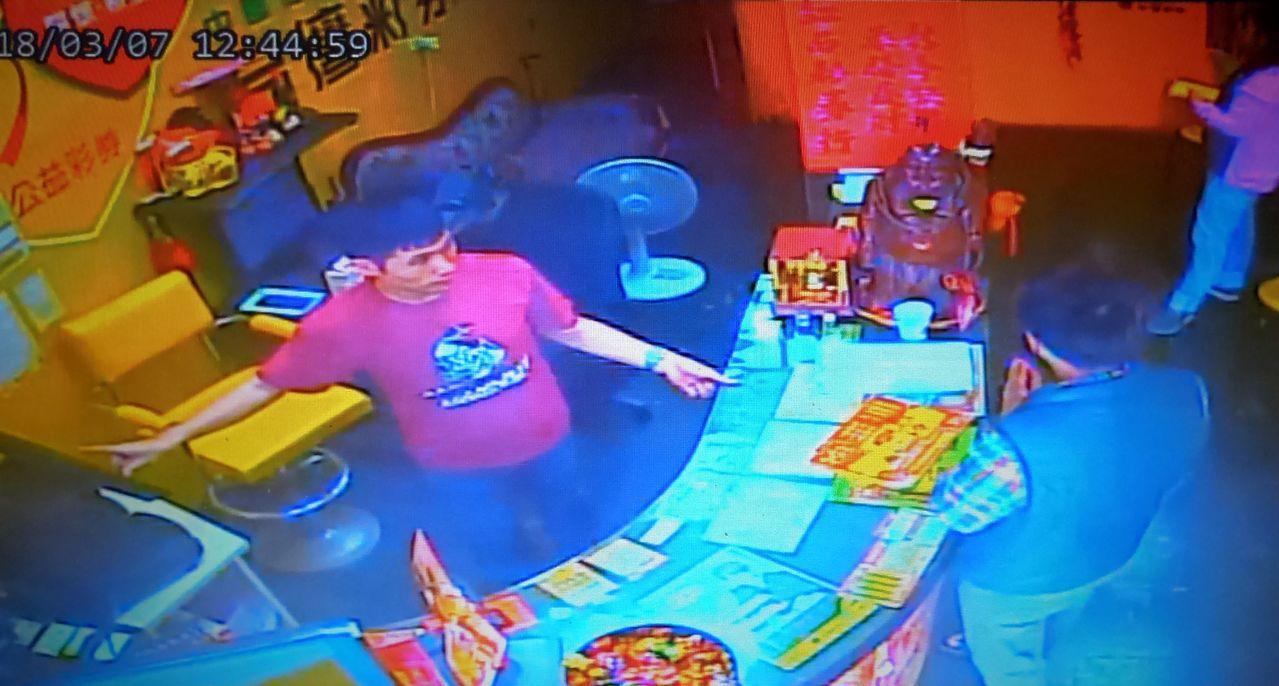 翁女(右下)膜拜著彩券行櫃檯上的彌勒佛,佯裝虞誠買彩券。記者林保光/翻攝