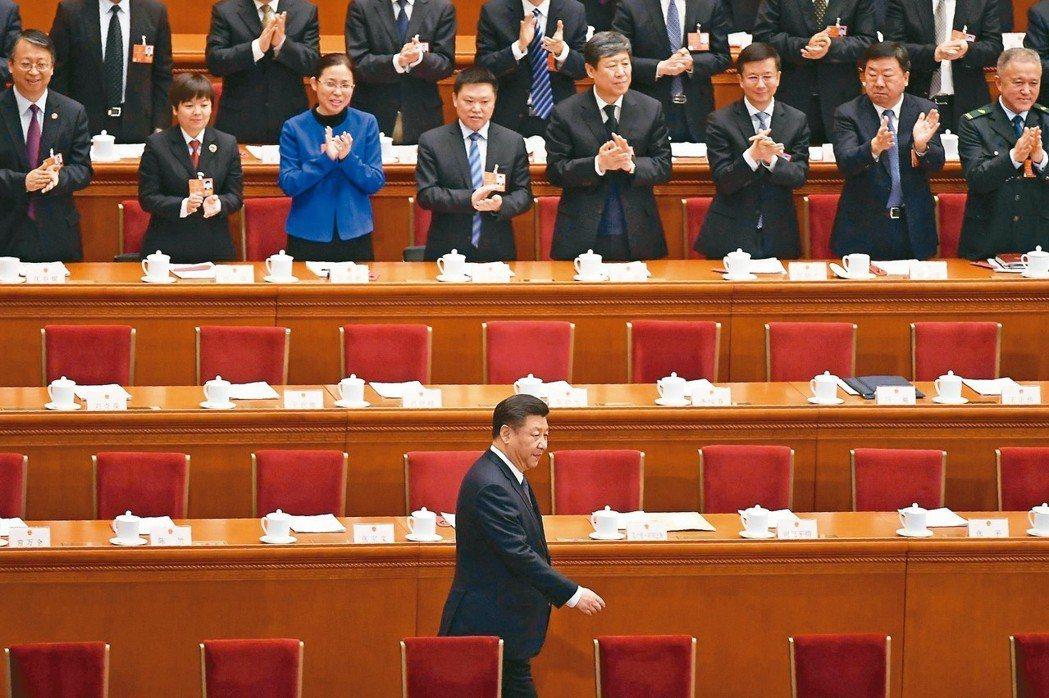 大陸國家主席習近平在修憲案投票前進入北京人民大會堂會場時,人大代表起立鼓掌。 法...