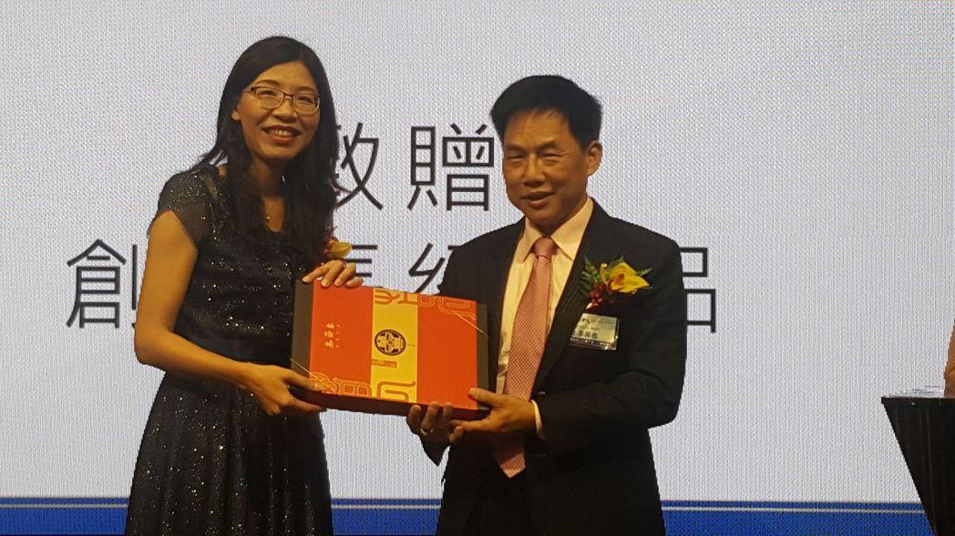 e總新任會長卓孝琪(左)代表全體會員致贈禮物給創會長李萬進 劉立諭/攝影