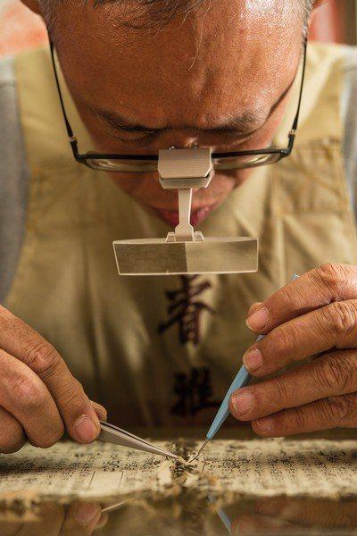 吳哲叡正聚精會神的進行修復工作。