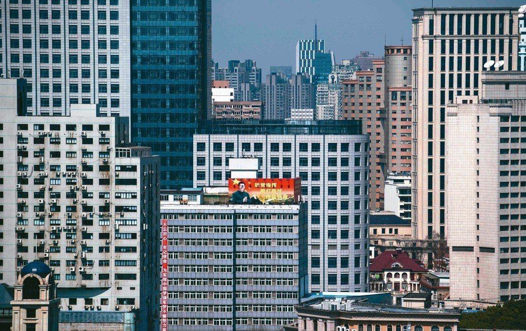 大陸全國人大前天剛通過修憲案。上海市區裡一棟高聳大樓張貼的宣傳畫布上,印著國家主...