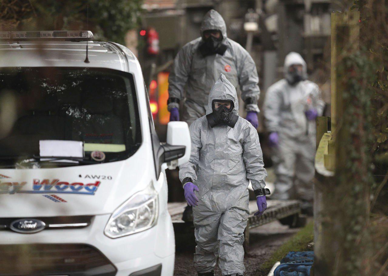 穿著防護衣的調查人員12日將一輛可疑的白色休旅車移走。美聯社