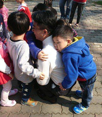 後塘國小校長葉炳成像「人體吸塵器」 每個小朋友都要抱抱。圖片/讀者提供